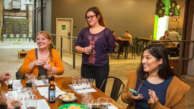 Dee Gedlen (center) talks about the history of a porter-style beer last month with Jessica Sobojinski (left) and Yeimidy Lagunas during a beer class at Third Space Brewing.