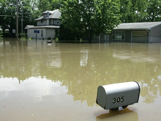 Floodwaters partially submerge a mailbox and homes on 5th Street in Coralville on Friday, June 13, 2008.