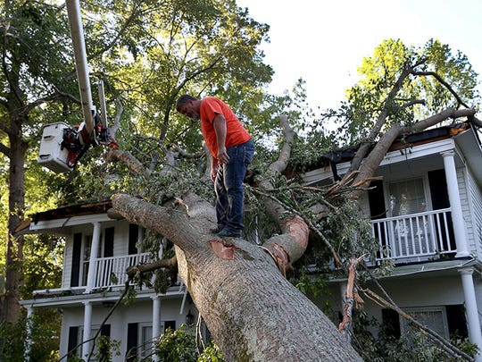 Rodney Stanford from Brewer Tree Service works on removing a tree that is resting on a home after a tornado struck on Monday, on April 30, 2014 in Tupelo, Mississippi.
