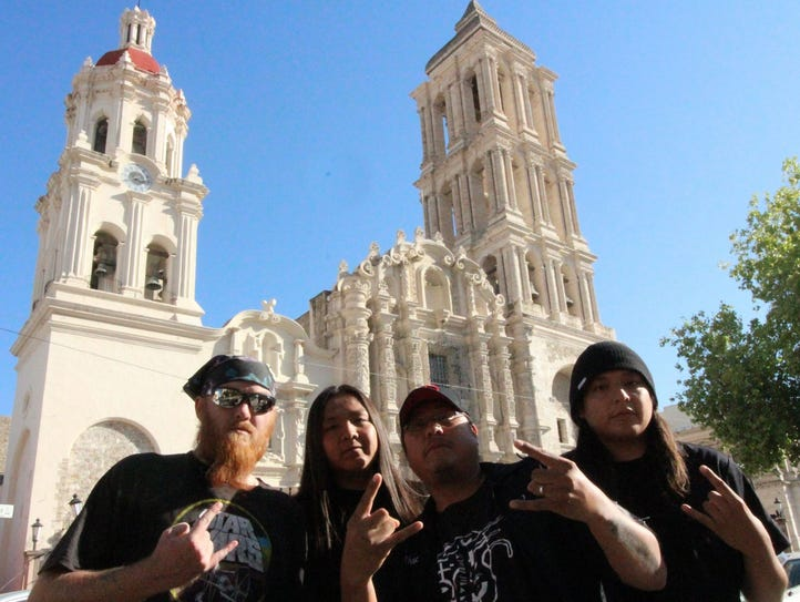 The members of Signal 99 pose before a cathedral in