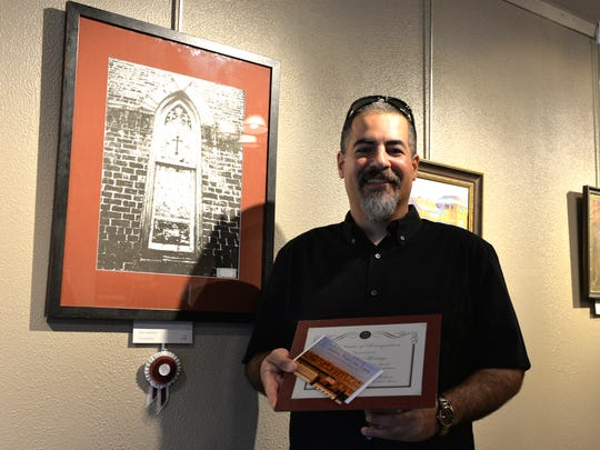 Lebanon artist Iggy Montijo holds the award he received after placing second in the second annual Paint the Town juried exhibition, held at Lebanon Picture Frame & Fine Art, 45 S. Eighth St., Lebanon, on April 1, 2016.