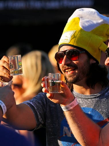 Blake Lew and Stephen Waicul take part in a toast at the Great Arizona Beer Festival Saturday, April 18, 2015 in the outfield of Sloan Park in Mesa, Ariz.