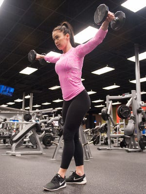 Katy Hearn, of Louisville, Ky., performs a shoulder exercise at the the Louisville Athletic Club in Louisville, Ky.
