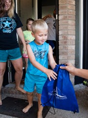 One of the teachers gives 5-year-old Drew Doherty a bag of school supplies before the start of the school year.