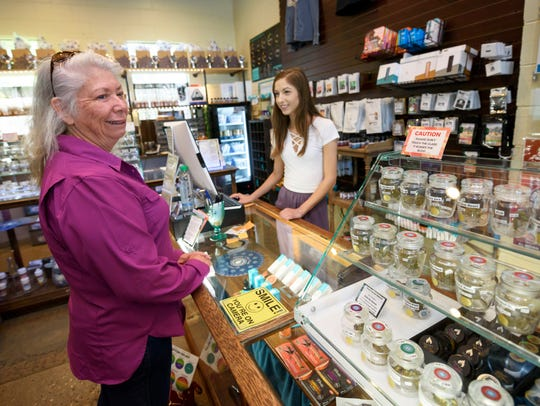 Manager Trisha Stevens, right, makes a sale to customer