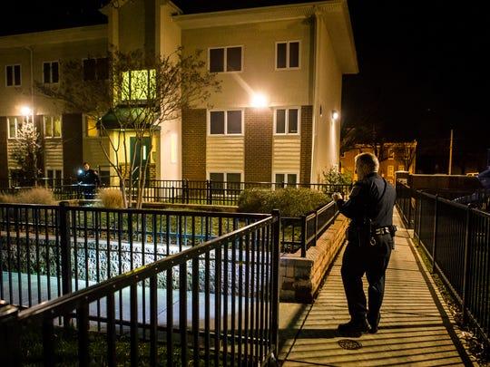 Sgt. Bill Schmid walks through a court year with other members of the Wilmington Police Department as they look for evidence of a shooting scene following a ShotSpotter call on Sunday night, Dec. 18, 2016.