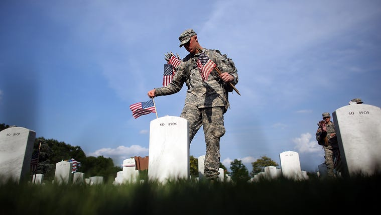 ARLINGTON, VA - MAY 24:  Members of the 3rd U.S. Infantry Regiment place American flags at the graves of U.S. soldiers buried in Section 60 at Arlington National Cemetery in preparation for Memorial Day May 24, 2012 in Arlington, Virginia. 'Flags-In' has become an annual ceremony since the 3rd U.S. Infantry Regiment (The Old Guard) was designated to be an Army's official ceremonial unit in 1948. Every available soldier in the 3rd U.S. Infantry Regiment participates in these events.  (Photo by Win McNamee/Getty Images)