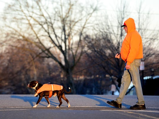 Edward Rose, of Hasbrouck Heights, walks his rescue three year old pit bull, Troy, in matching orange winter wear along Boulevard Tuesday morning on December 26, 2017. Rose's sister made Troy's winter coat after a delivery person did not see him and tripped over him at night.