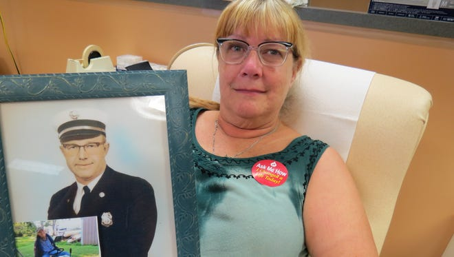 Vicki Ponder Parks holds a photo of her father, Mel Ponder, while donating blood during the August 2015 Cuffs and Ladders Blood Drive.