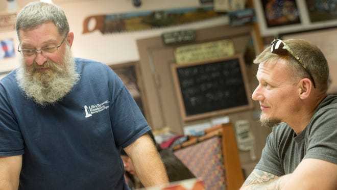 Jacob Norton, right, who is in recovery from heroin addiction, looks on as Bob Allen shares a story during Tuesday night dinner at Life's Beacon, a nonprofit in York that provides housing as well as other skills for people in recovery from drugs and alcohol. Allen is the director of the life skills house. News this month about an uptick in fatal overdoses in York County has some in the recovery community thinking about their own experiences and what they want to do to help others.