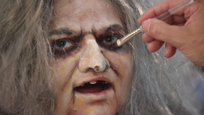 Gillian Stine, 17, transforms into the face of Grandmama , with a prosthetic nose, as make-up artist Rob Volsky touches up her eyes at his home in Vero Beach. Cast members for Port St. Lucie High School's summer production of the The Addams Family were practicing the transformation into their characters with the help of Volsky.