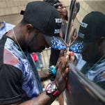 Mourner Tramell Metz pauses at the hearse of Samuel Dubose before his casket is transported to a cemetery during funeral services at the Church of the Living God in the Avondale neighborhood of Cincinnati, Tuesday, July 28, 2015. Dubose was fatally shot by a University of Cincinnati police officer who stopped him for a missing license plate.