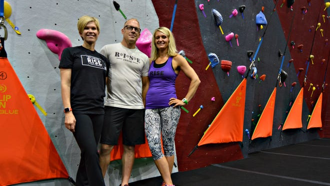 Amanda and Ryan Peters, and Jen Kaufmann, owners of RISE Fitness + Adventure in Rehoboth Beach, pose in front of the gym's 34-foot-tall rock wall.