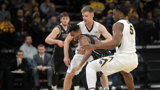Iowa's Brady Ellingson and Tyler Cook (5) knock the ball away from Northern Illinois' Dante Thorpe during their game at Carver-Hawkeye Arena on Friday, Dec. 29, 2017.