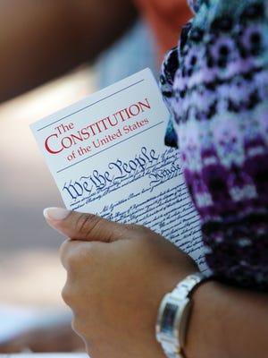 A UL student holds a free copy of the U.S. Constitution as other students, faculty and community leaders read the U.S. Constitution aloud Tuesday in the UL Quad in commemoration of Constitution Day in 2013