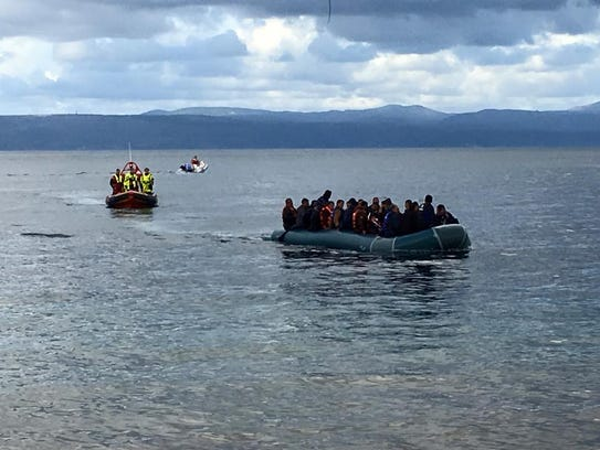 Refugees are jammed into a raft while fleeing to the
