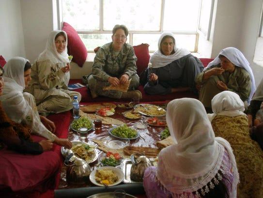 A group of Afghan women and Capt. Jillian Torango from