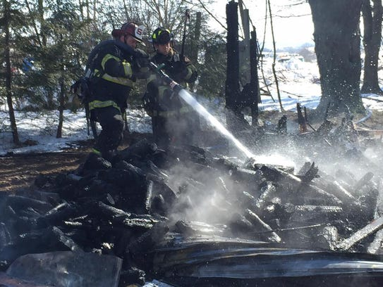 Firefighters spray debris from a house fire at 16957