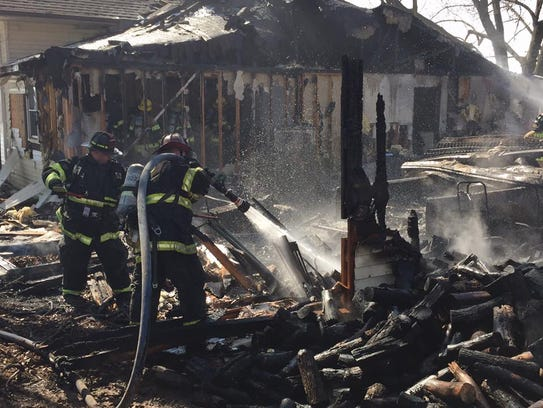 Firefighters spray water on debris from a house fire