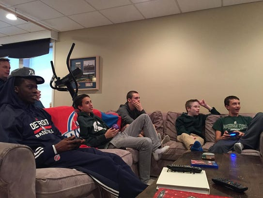 Pistons guard Reggie Jackson plays an NBA video game