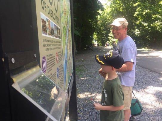 Joe Murphy looks at a sign with his grandson, Aidan