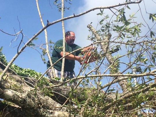 Jason Patzer works on some tree limbs after Hurricane