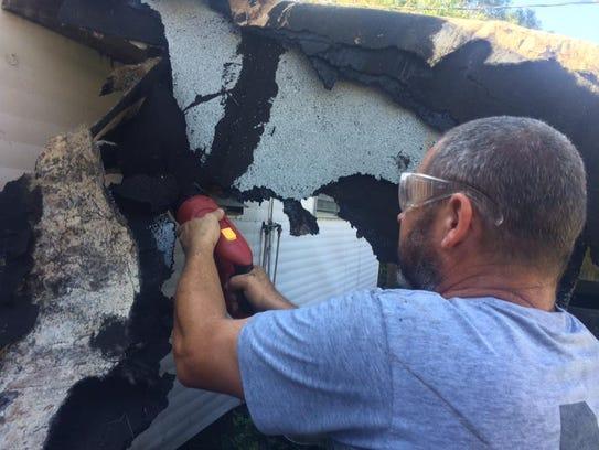 Jason Cranman cuts away some debris.