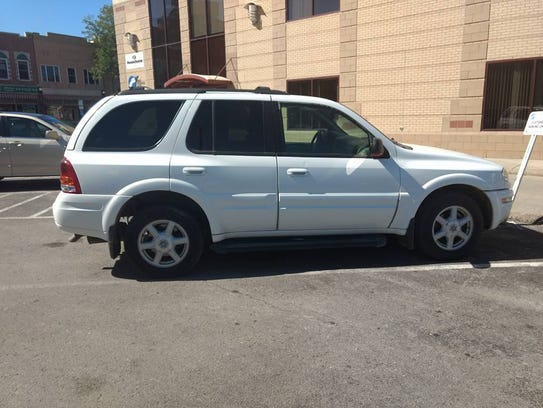 A white early 2000s Oldsmobile Bravada that police