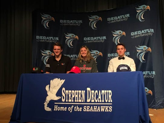From left: Tristan McDonough, Lily Belle Baker and Mitchell Orf sign their letters of intent to play at the college level on Nov. 8, 2017.