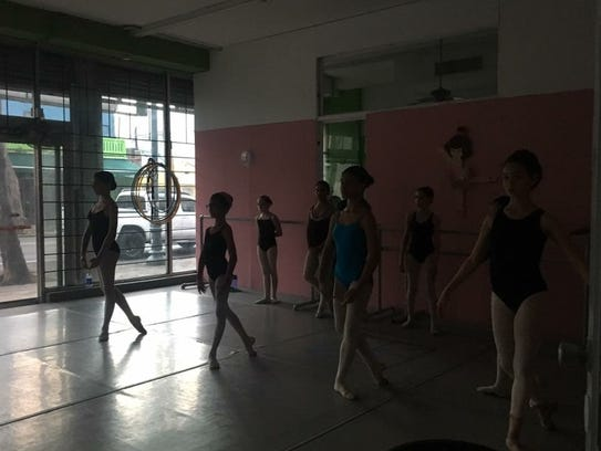 Dancers in the darkened Mauro Youth Ballet Company
