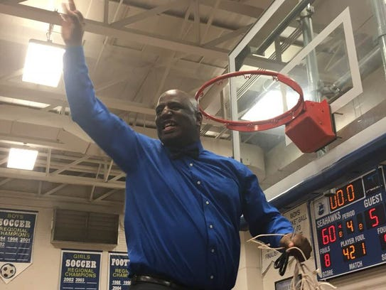Decatur coach BJ Johnson cuts down the net following
