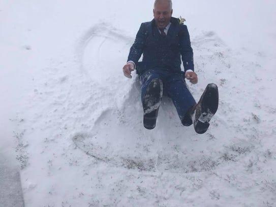 Scott Christensen makes a snow angel at his daughter's
