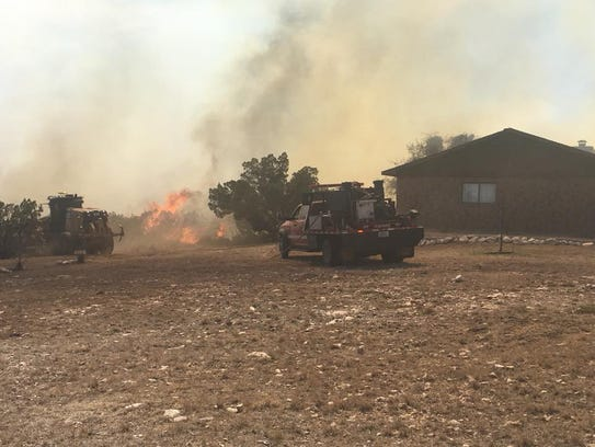 The Ratliff Road Fire south of Big Spring threatens a house on Monday.