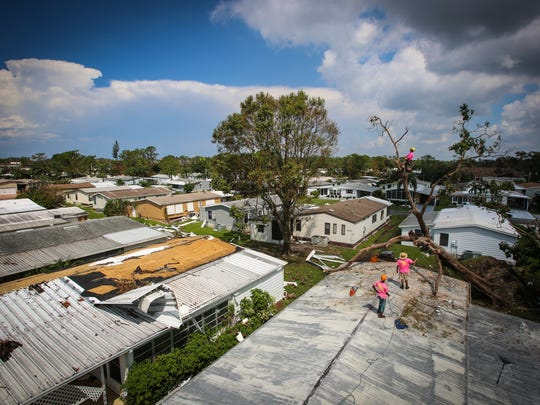 "Tarrelle Johnson, 27, left, Josh Walker, 25, center, and Nick Dedominicis, 24, on the tree, work to remove a tree that fell on Donna Gomes' home in North Naples Thursday, Sept. 14, 2017. The trio work for Elite Treehouse, a company based in Canton, Georgia, which was contracted to help clean up the Landmark Naples neighborhood. ""We realized how much destruction was down here and wanted to help out,"" Walker said."