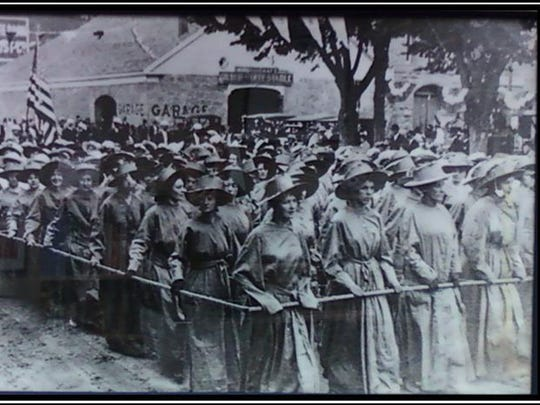 Top, this undated photo of marching suffragists hangs