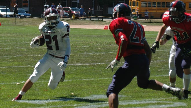 Scarsdale halfback Sam Squadron (white) attempts to run past Ketcham defensive back Brandon Chavarria (red, 21) during a game at Scarsdale High School on Saturday, September 5, 2015. Scarsdale defeated Ketcham 35-14.