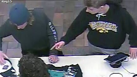An image from surveillance video shows two men suspected of burglarizing a vehicle and fraudulently using a stolen credit card.
