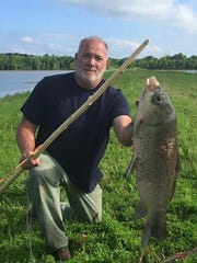 Lyle Shaulis with a 30-pound buffalo carp he shot with a bow he made from a hickory sapling.