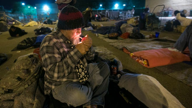 Terry Brooks, 50, lights a cigarette while staying at the East Lot, a parking lot that serves as Maricopa County's current solution for emergency shelter, February 4, 2015.