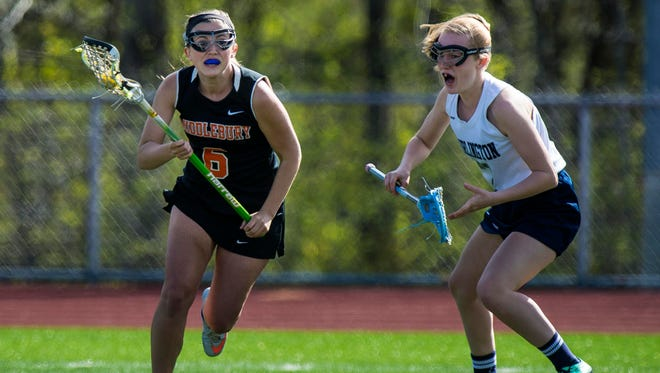 Middlebury's Emma Donahue, left, gets away from Burlington's Malin Hilleman in Burlington on Tuesday, May 17, 2016.
