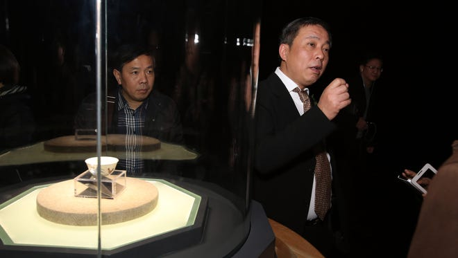 "In this Dec. 18, 2014 photo, Chinese billionaire and art collector Liu Yiqian, right, speaks at an opening ceremony in Shanghai, China, for the exhibition of a $36 million Ming Dynasty tea cup, at left, he bought and paid for with his American Express card. Liu was the winning bidder for Amedeo Modigliani's ""Reclining Nude"" at a Christie's auction earlier this month - offering $170.4 million - and when the sale closes he'll be putting it on his American Express card. (Chinatopix via AP) CHINA OUT"