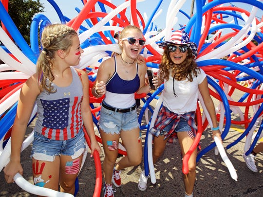 Girls from New Hope Church sport red, white, and blue balloons while marching in the Urbandale Fourth of July parade in 2018.