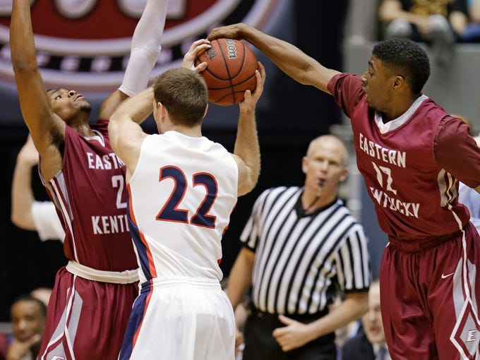 Eastern Kentucky guard Marcus Lewis (12) steals the ball from Belmont guard Reece Chamberlain (22) during the first half of an NCAA college basketball game for the championship of the Ohio Valley Conference men's tournament, Saturday, March 8, 2014, in Nashville, Tenn. At left is Eastern Kentucky guard Corey Walden (2). (AP Photo/Mark Humphrey)
