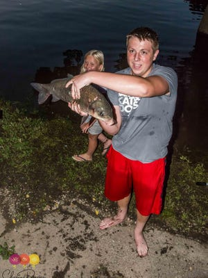 Mason Noskowiak, 14, of Springfield, briefly holds the carp he caught — three days after cutting his tangled fishing line.