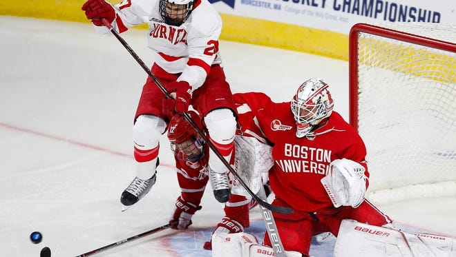 Cornell's Morgan Barron (27) screens the shot on Boston's Jake Oettinger, right, during the third period of an NCAA college hockey tournament regional game in Worcester, Mass., Saturday, March 24, 2018. Boston won 3-1. (AP Photo/Michael Dwyer)