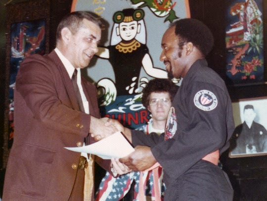 Charles Moulden, right, receives his orange belt from
