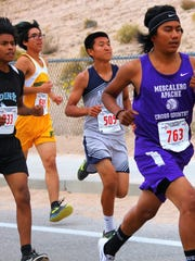 Mescalero's Alex Kaydahzinne, right, tries to pull away from the pack.
