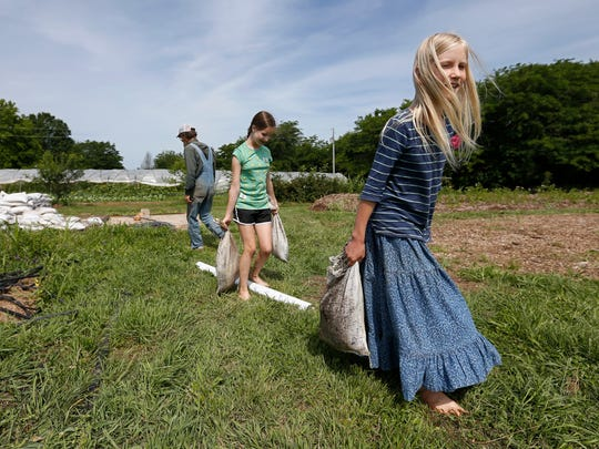 Anna Millsap, right, and Rebecca Loya carry sand bags