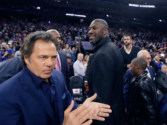 Former Detroit Pistons player Ben Wallace arrives at courtside next to team owner Tom Gores, left, before the Pistons' NBA basketball game against the Golden State Warriors, Saturday, Jan. 16, 2016 in Auburn Hills, Mich. (AP Photo/Carlos Osorio)