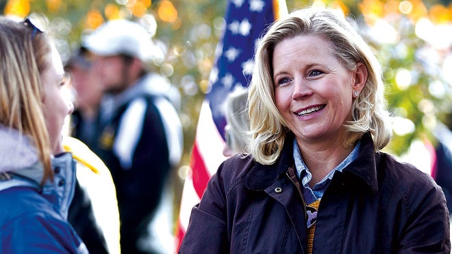 U.S. Senate candidate Liz Cheney talks with Laramie residents prior to the start of the University of Wyoming homecoming parade in Laramie, Wyo., on Oct. 12.